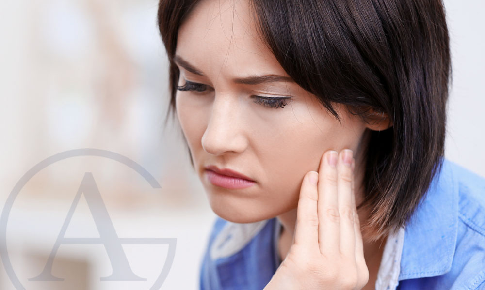 woman holding jaw suffering from tmj pain